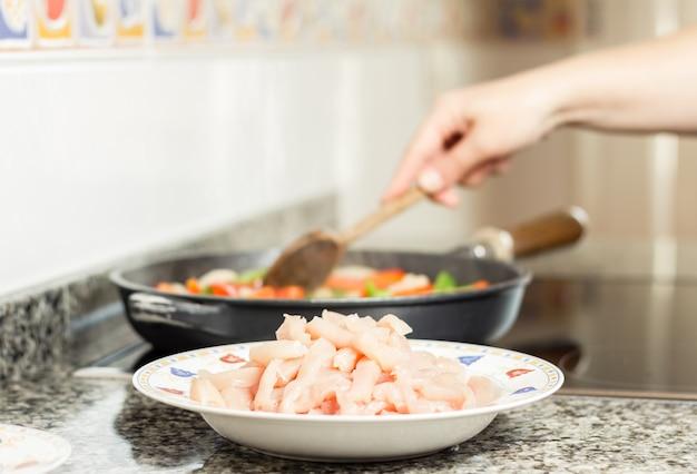 Блюдо из сырого цыпленка и женская кулинария на сковороде