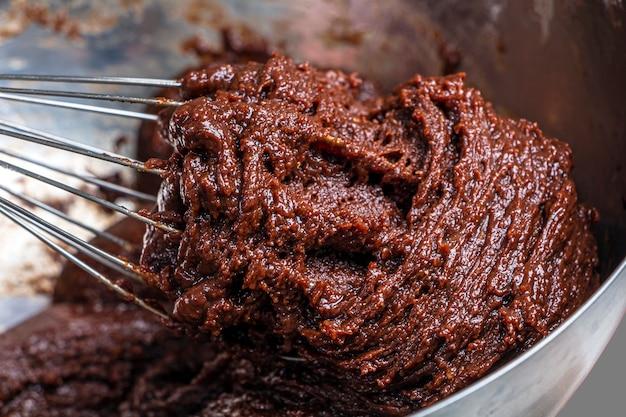 ボウルと泡だて器で生チョコレート生地。ホリデーフードのコンセプト、自家製の子供用クッキー、ジンジャーブレッド。閉じる。