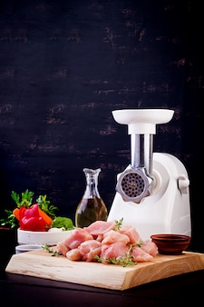 Raw chopped chicken breast fillets on wooden cutting board  and meat grinder. copy space