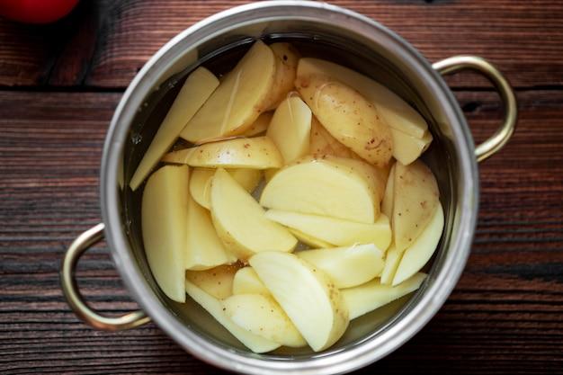 Сырой нарезанный картофель в кастрюле с водой. подготовка к приготовлению.