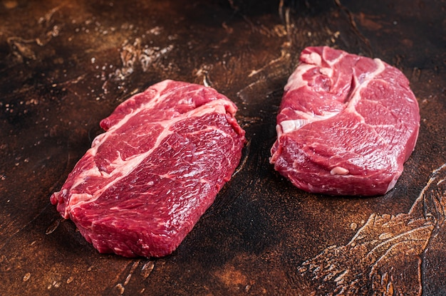 Raw chuck eye roll beef steak on butcher table. dark table. top view.