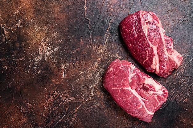 肉屋のテーブルに生のチャックアイロールビーフステーキ
