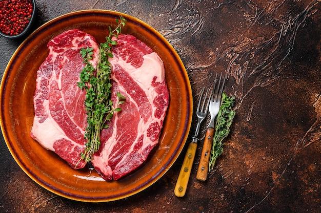 生のチャックアイロールステーキは有機牛肉です。暗い背景。上面図。スペースをコピーします。