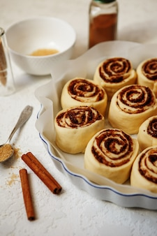 Сырые булочки с корицей в форме для запекания перед выпечкой