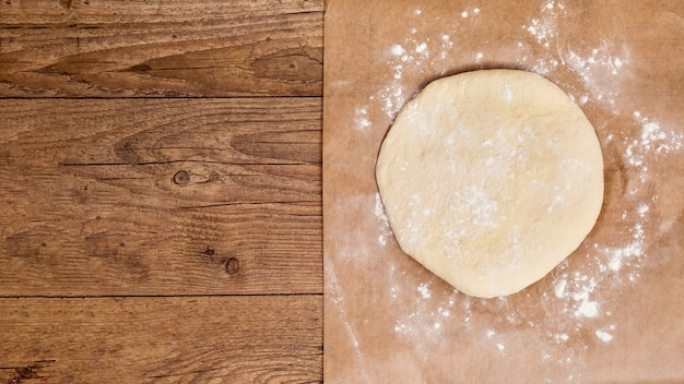 Raw circular flatten dough on parchment paper over the wooden table