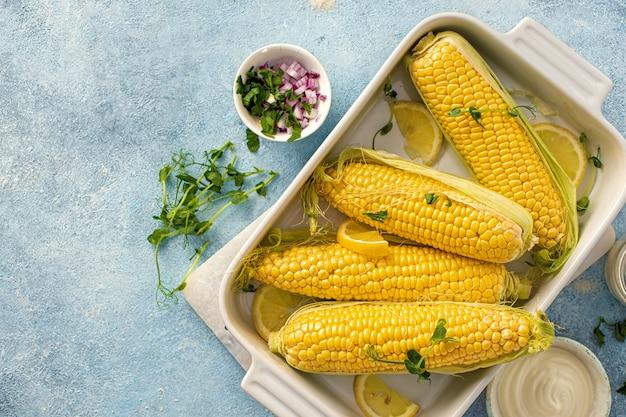 Raw cob corn in baking dish for preparing healthy vegetarian food top view
