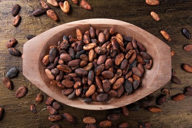 Сырые какао-бобы внутри деревянного подноса с деревенским фоном