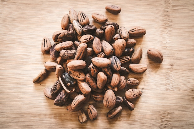 Raw cocoa beans on a wooden board