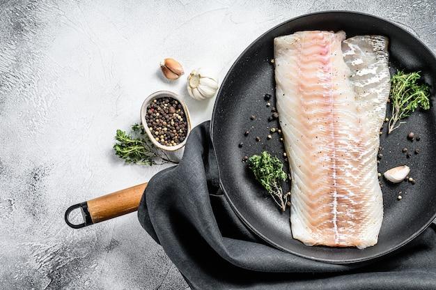 Сырое филе трески с тимьяном и зеленью на сковороде. готовим свежую рыбу. серый фон. вид сверху. скопируйте пространство.