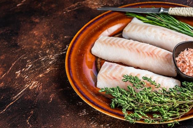 Сырые стейки из филе трески на деревенской тарелке с тимьяном и солью. темный фон. вид сверху. скопируйте пространство.