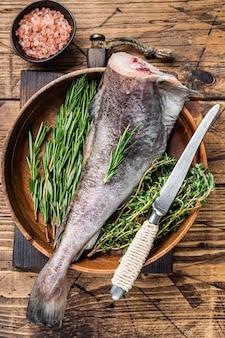 Сырая треска или треска в деревянной тарелке с зеленью