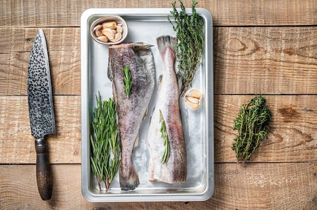 Сырая треска целая рыба в стальном кухонном подносе с тимьяном и розмарином. деревянный фон. вид сверху.