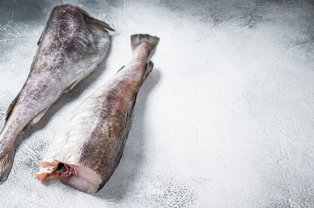 Рыба сырой трески целая на кухонном столе. белый фон. вид сверху. скопируйте пространство.