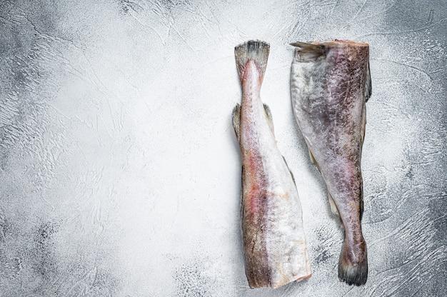 Сырая треска целая рыба на кухонном столе