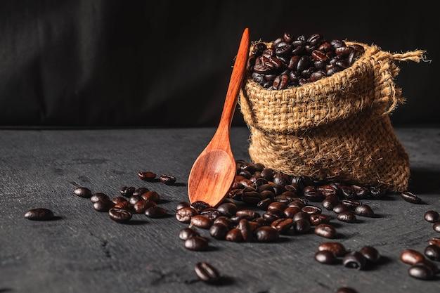 Сырые кофейные зерна в мешке мешок на черном фоне.
