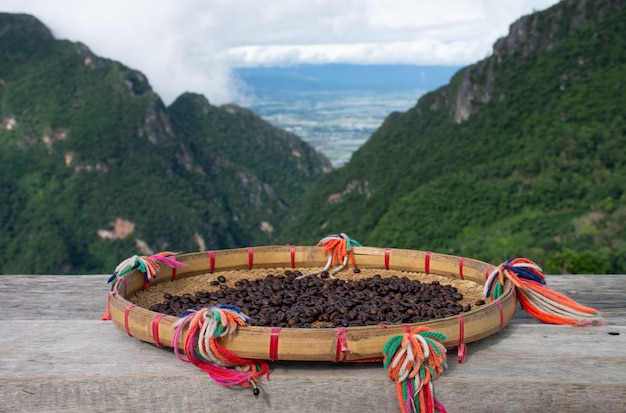 Raw coffee beans sun-dried on a wooden table with beautiful mountain views in northern thailand.