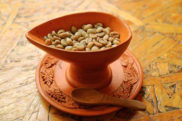 Raw coffee beans in a thai style terracotta bowl for homemade coffee