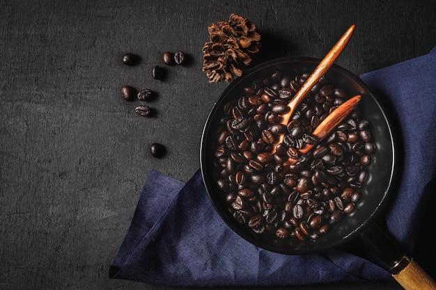 Сырой кофе, жаренный в кастрюле на черном фоне