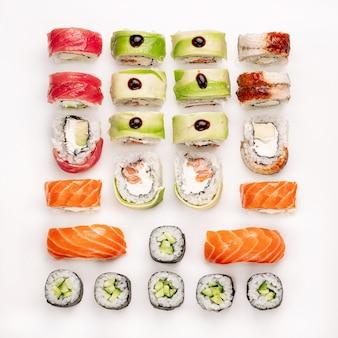 Сырые красочные суши на белом фоне. вид сверху. коллекция кусочков суши, изолированные на белом фоне