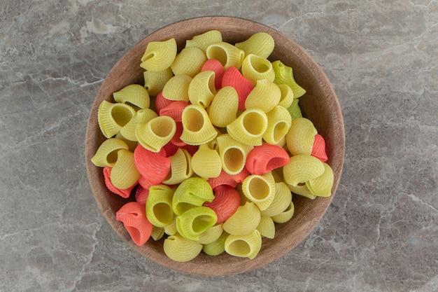 Сырые макаронные изделия conchiglie в деревянной миске.