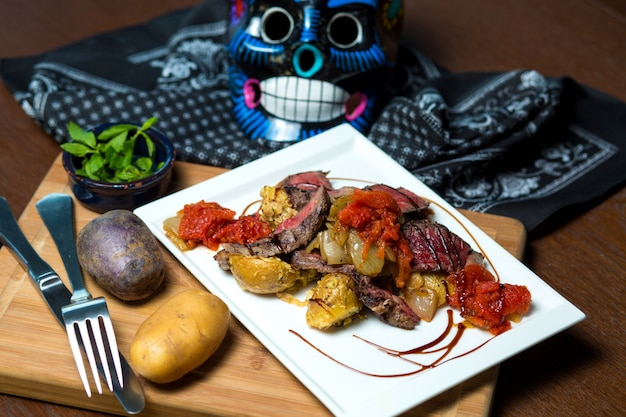 Raw cooked steak served with potato and tomato sauce