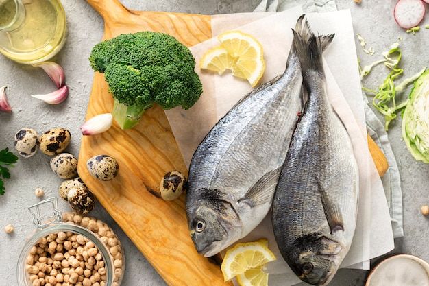 Raw cooking ingredients healthy food. fresh fish, vegetables, herbs and legumes on gray background top view
