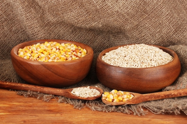 荒布のテーブルの上の木製のボウルに生のトウモロコシと小麦