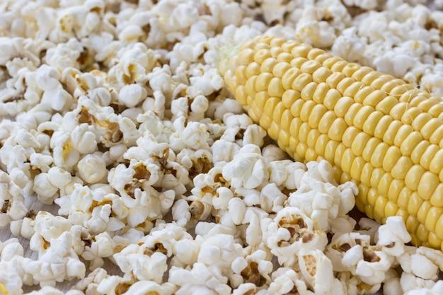Сырой кукурузный початок и попкорн, крупный план
