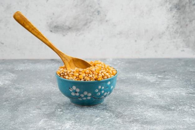 スプーンで青いボウルに生のトウモロコシの粒。