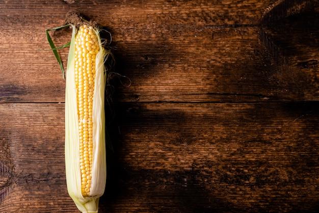 어두운 나무 배경에 원시 옥수수입니다. 건강 식품, 채식주의 개념입니다. 텍스트를 삽입할 위치입니다.