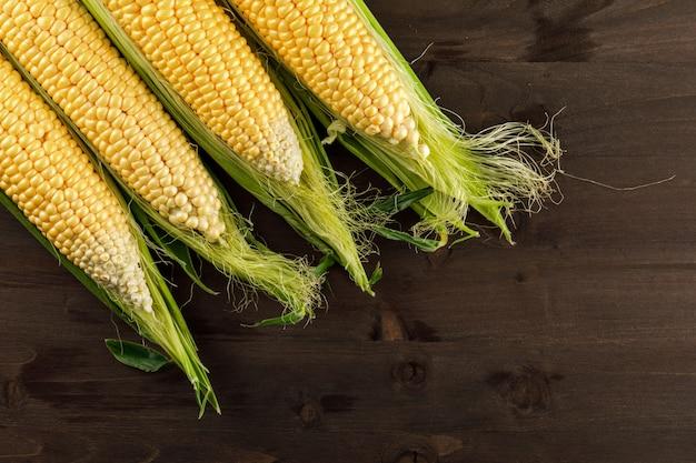 Сырье кукуруза на темный деревянный стол. плоская планировка