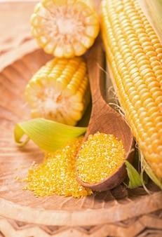 Сырая кукуруза с зелеными листьями на белой поверхности