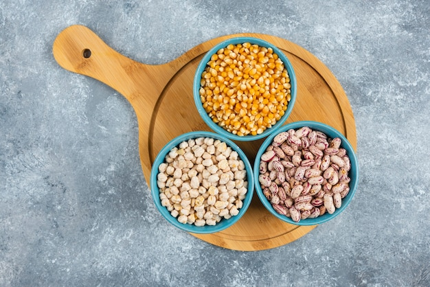 Raw corns, beans and chickpeas in blue bowls.