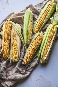 Сырые кукурузы, свежесобранные с зеленой кукурузой на деревенском столе старинный фон, вид сверху