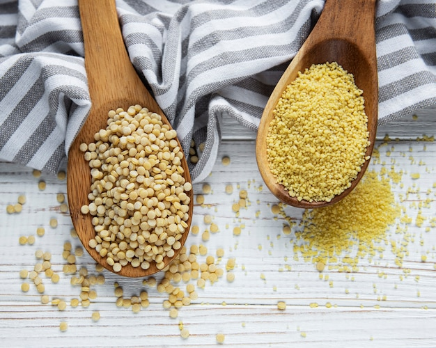 Raw couscous in a wooden spoons on the table