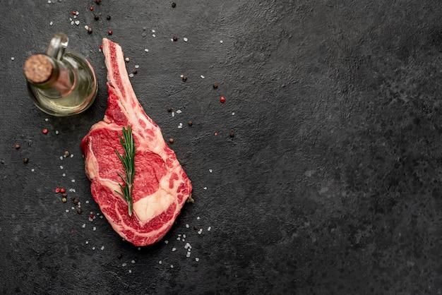あなたのテキストのコピースペースと石の背景にスパイスと生のカウボーイステーキ