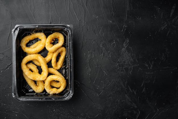 검은 색 어두운 돌 테이블 배경에 빵 부스러기 패키지 세트의 생 바삭한 오징어 링