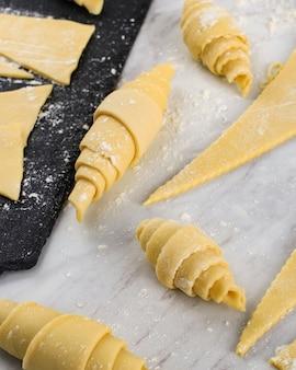 生クロワッサン、自家製クロワッサンを作るプロセス、家庭で焼く生クロワッサンの準備。白い大理石のテーブルの上にさまざまなサイズのクロワッサン。選択されたフォーカス