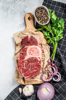 Raw cross cut veal shank, osso buco with spices and herbs. ossobuco meat. gray background.
