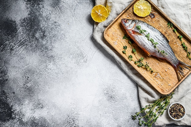 Raw crucian carp on a wooden tray. river organic fish. gray background. top view. space for text.