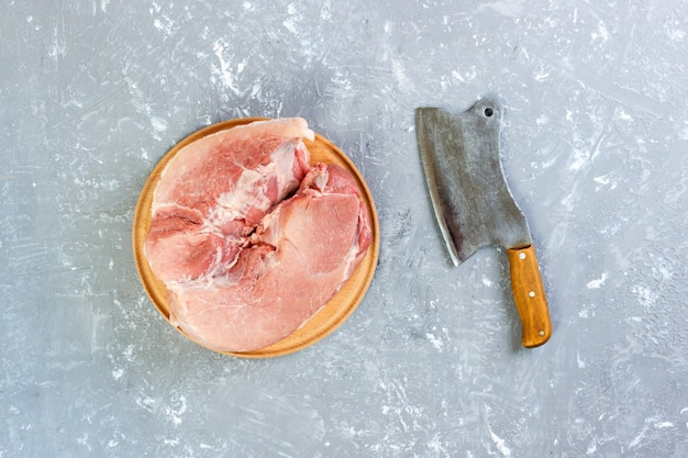 Raw cut of pork shoulder on board with knife or kitchen ax. cleaver with fresh raw meat on gray concrete background