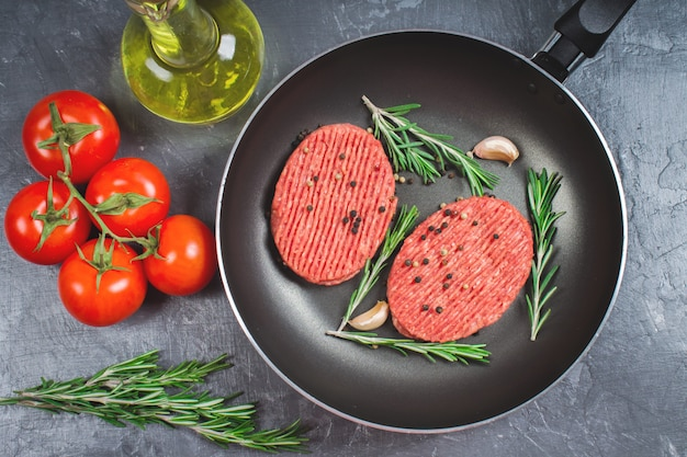 Raw cutlets pan with rosemary and garlic. grey marble background.