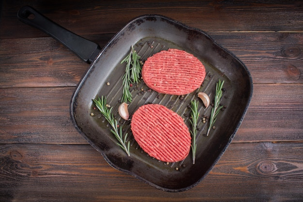 Raw cutlets pan with rosemary and garlic. wooden brown background.