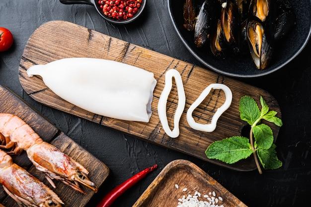 Сырое мясо каракатицы с ингредиентами для паэльи на черной бетонной поверхности