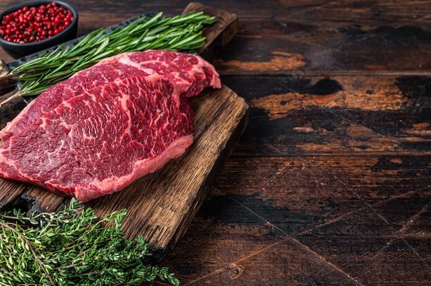 원시 덴버는 고기 식칼로 정육점 판에 검정 거스 쇠고기 스테이크를 자른다. 어두운 나무 배경입니다. 평면도. 공간을 복사합니다.