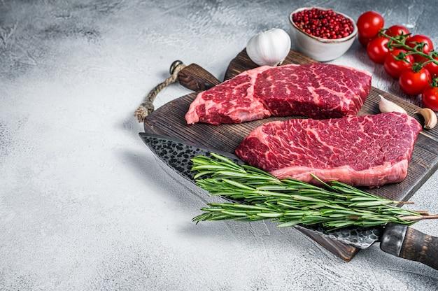 生のデンバーは、ハーブを使った肉屋のまな板でブラックアンガスのオーガニックステーキをカットしました。白色の背景。上面図。スペースをコピーします。