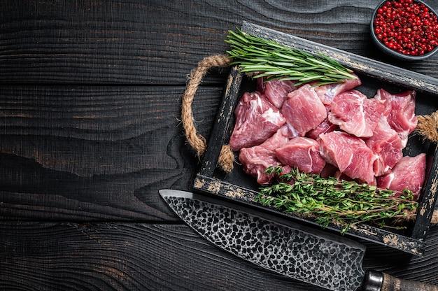 Сырое нарезанное кубиками мясо детенышей свинины со специями в деревенском подносе. черный деревянный стол. вид сверху. скопируйте пространство.