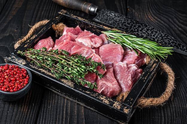 Сырое нарезанное кубиками мясо детенышей свинины со специями в деревенском подносе. черный деревянный стол. вид сверху.