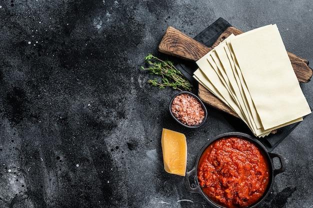 台所のテーブルでイタリアのラザニアを調理するための生のさまざまな材料。黒の背景。上面図。スペースをコピーします。