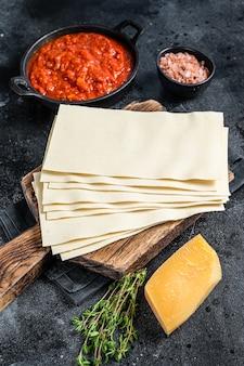 台所のテーブルでイタリアのラザニアを調理するための生のさまざまな材料。黒の背景。上面図。